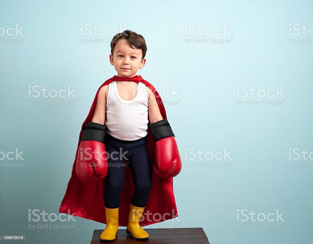 Cute boy wearing boxing gloves stock photo
