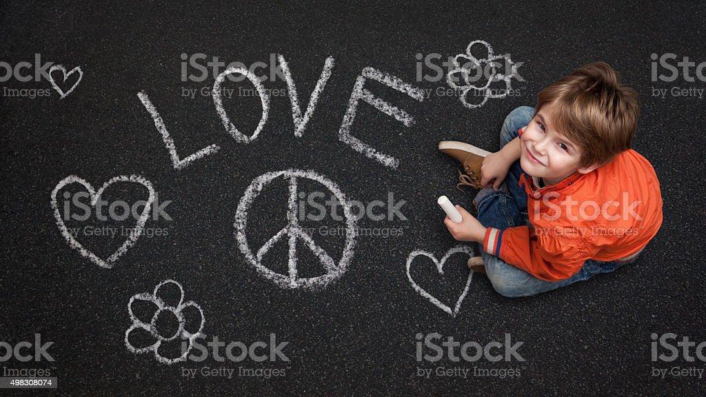 Cute Boy, with Chalk on Street/Tarmac, Love Peace Flowers Happin stock photo