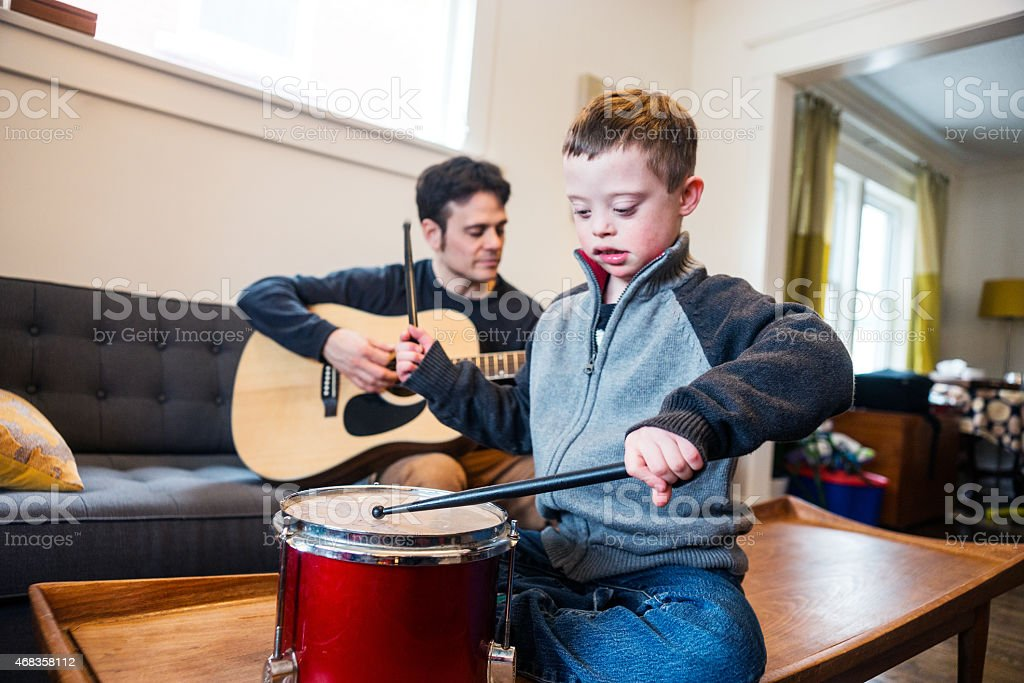 Cute boy with Down Syndrome playing music with dad. stock photo