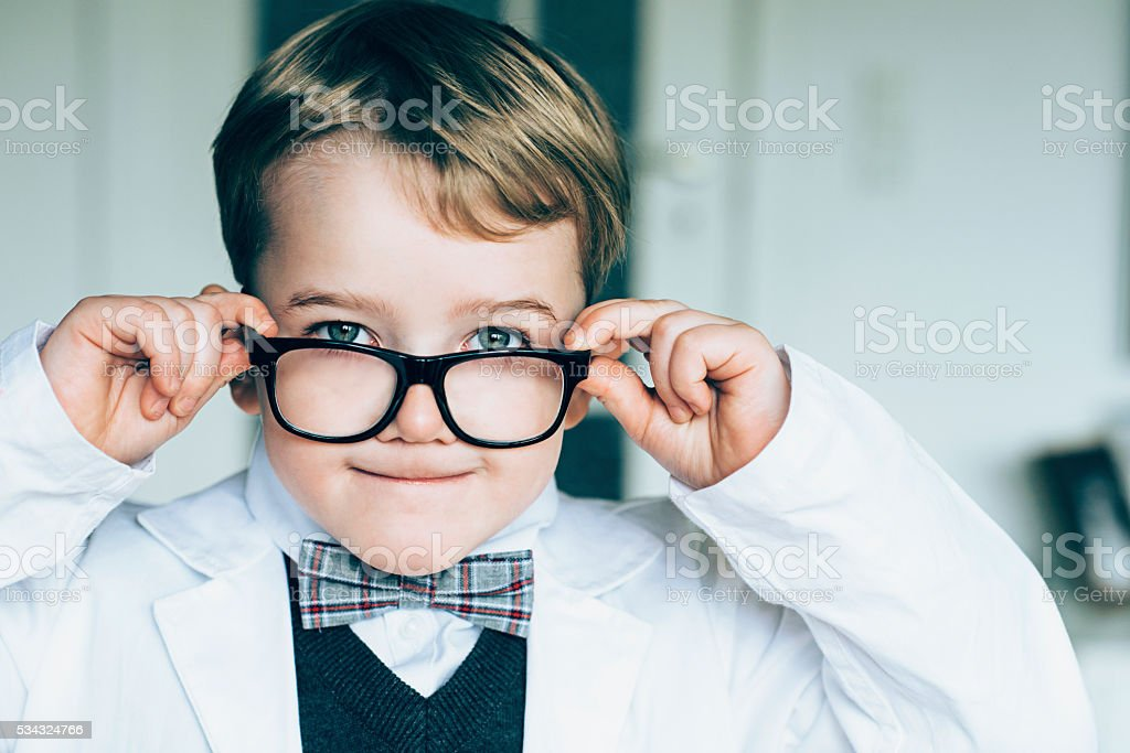 Cute boy with glasses and bow tie makes funny face stock photo