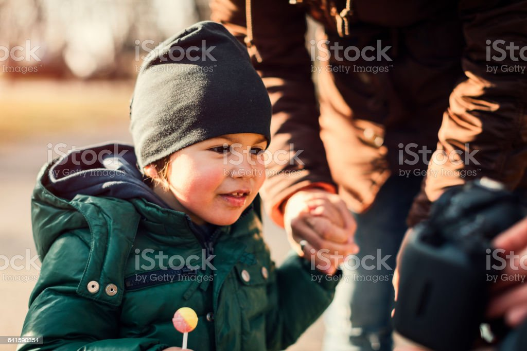 Cute boy with lollipop in the park stock photo