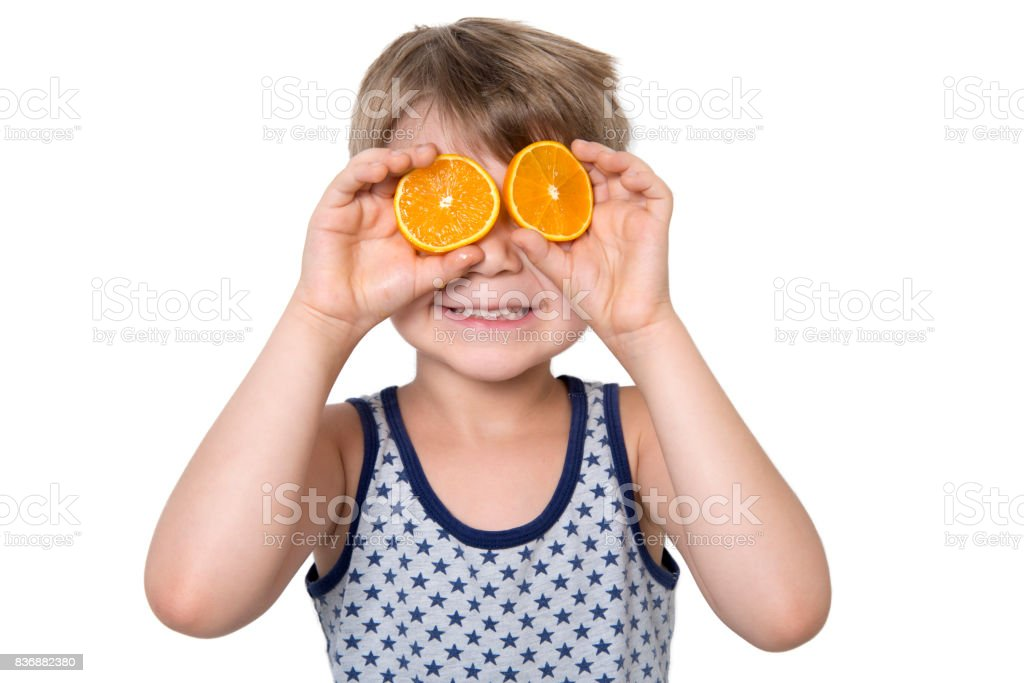 Cute Boy With Two Slices Orange On Eyes stock photo