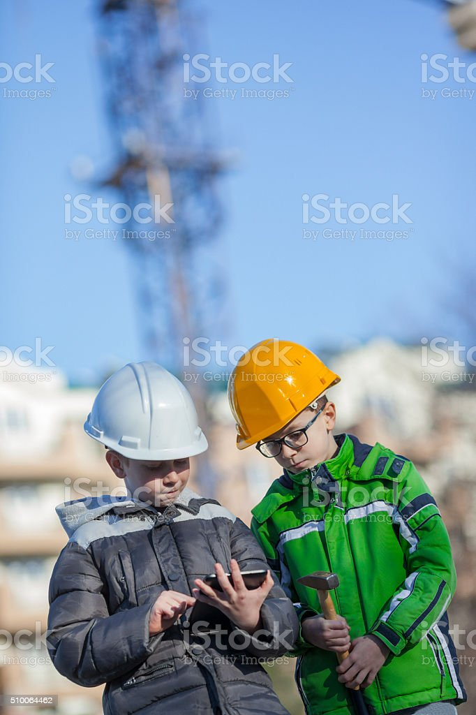 Cute boys builders with white and yellow helmet stock photo
