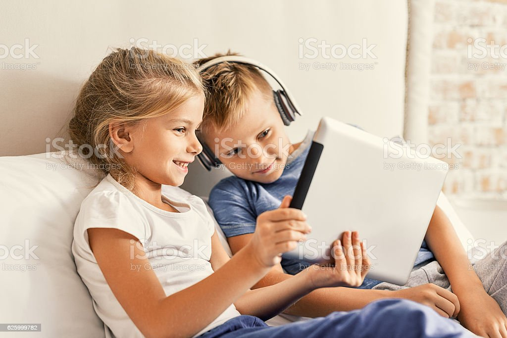 Cute brother and sister enjoying tablet at home stock photo