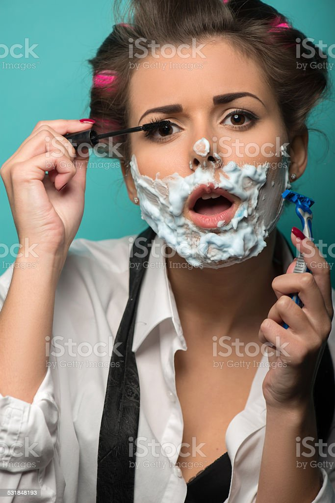 Cute brunette in hair curlers and foam posing with razor stock photo
