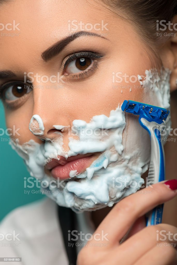Cute brunette in hair curlers posing with razor on blue stock photo