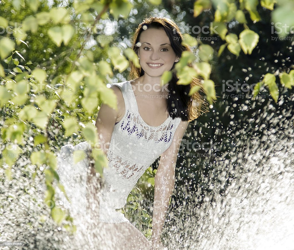cute brunette in white dress standing behind water splash royalty-free stock photo