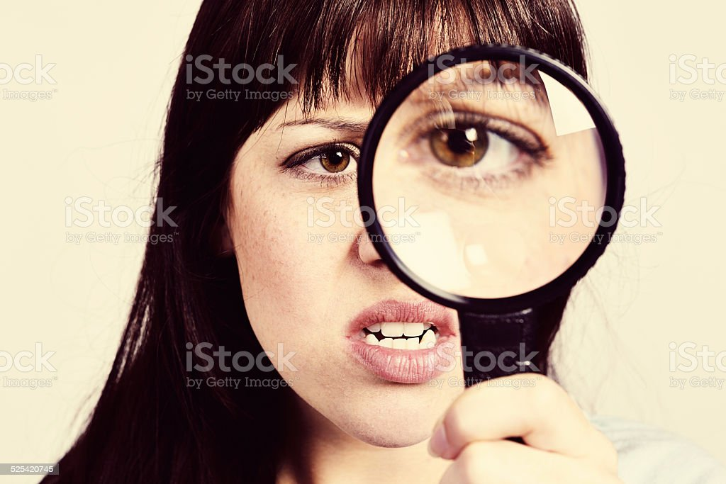 Cute brunette unhappy with what she sees through magnifying glass stock photo