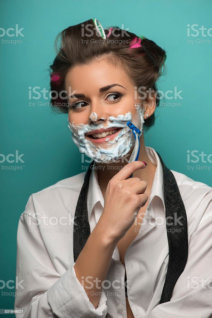 Cute brunette woman in hair curlers posing with foam on stock photo