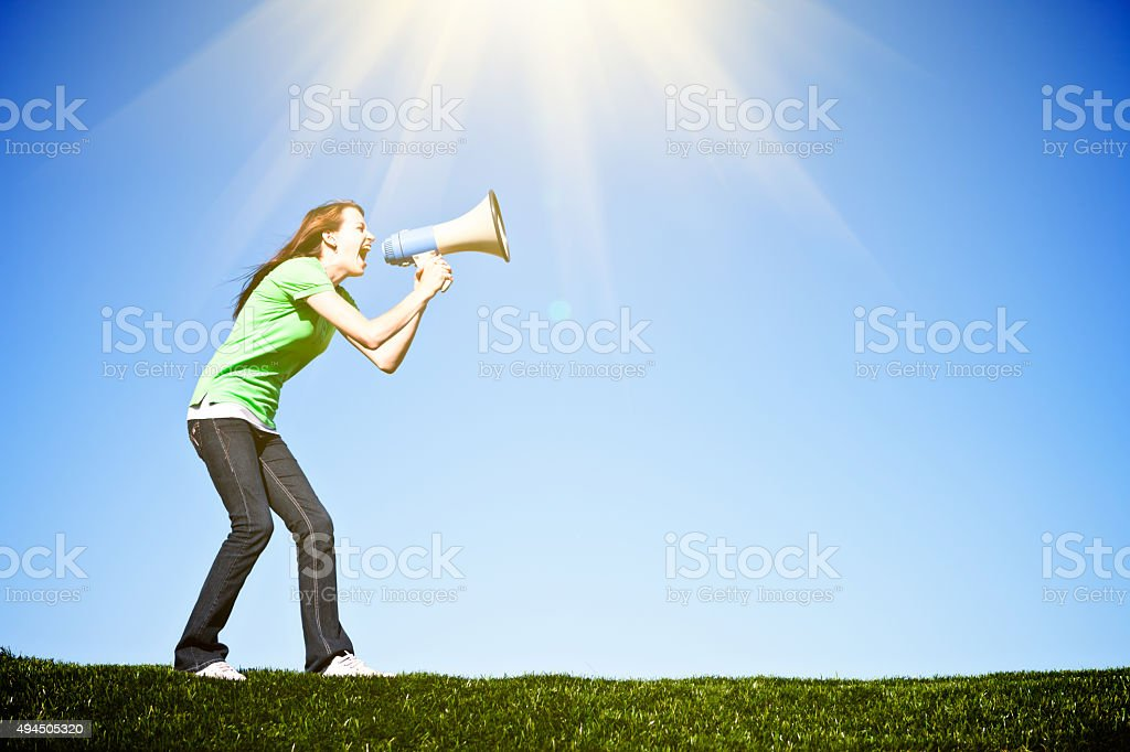 Cute brunette yells enthusiastically into bullhorn, coaching, encouraging, or protesting stock photo