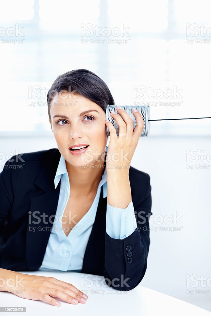 Cute business woman listening to a tin can phone royalty-free stock photo