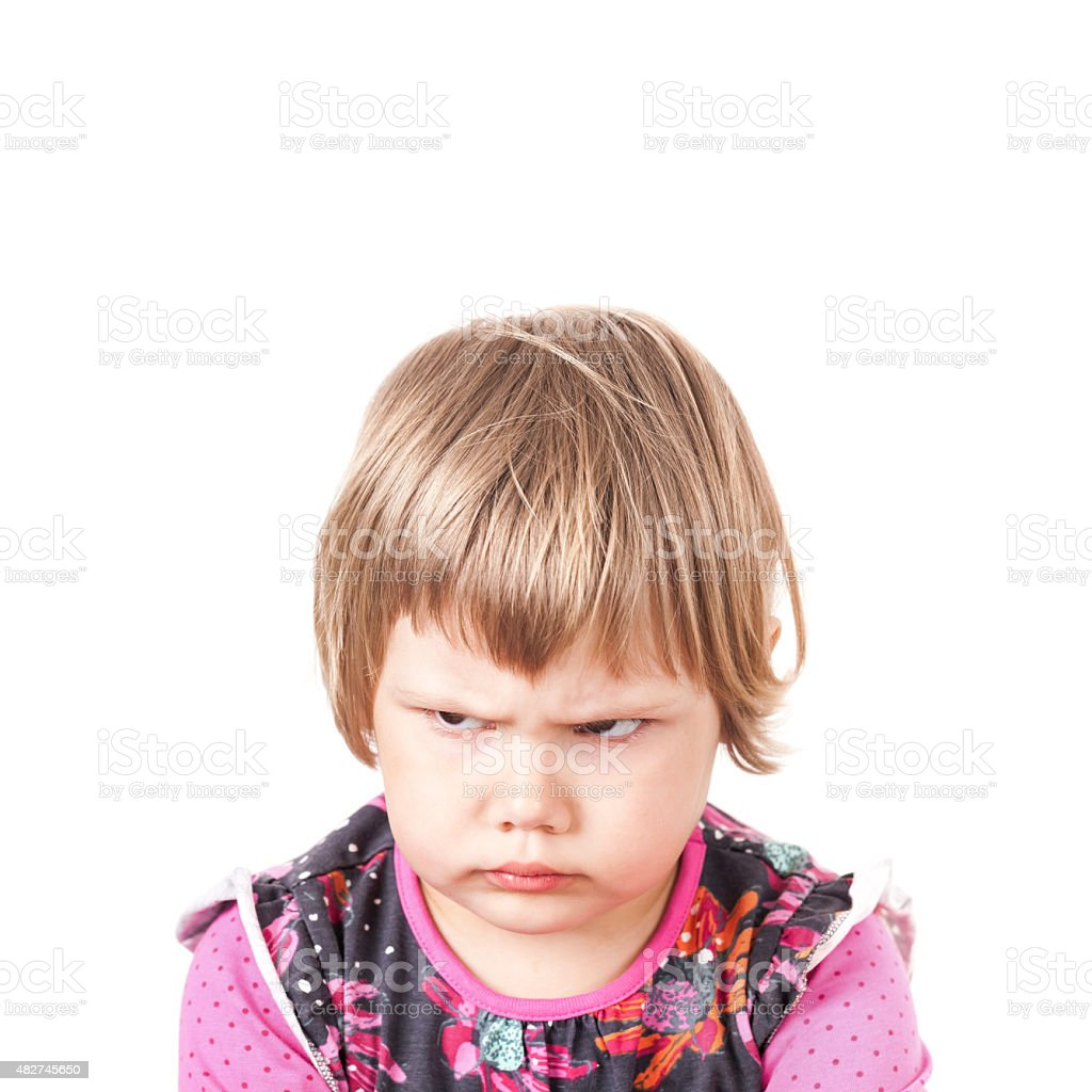 Cute Caucasian blond baby girl angry frowns stock photo