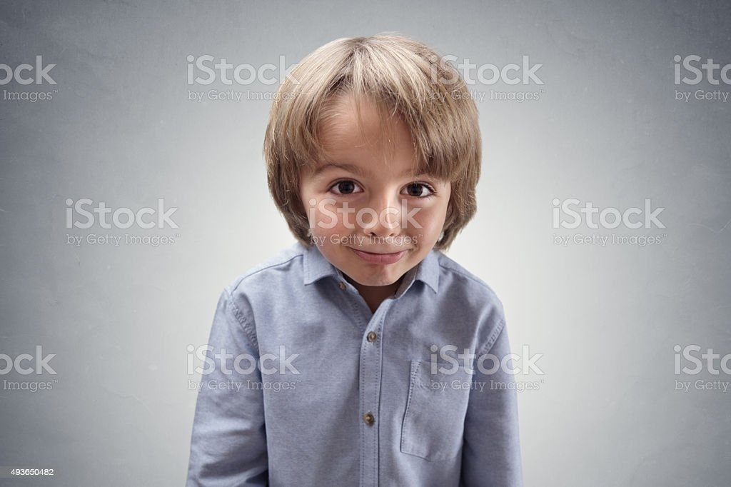 Cute cheeky boy with guilty expression stock photo