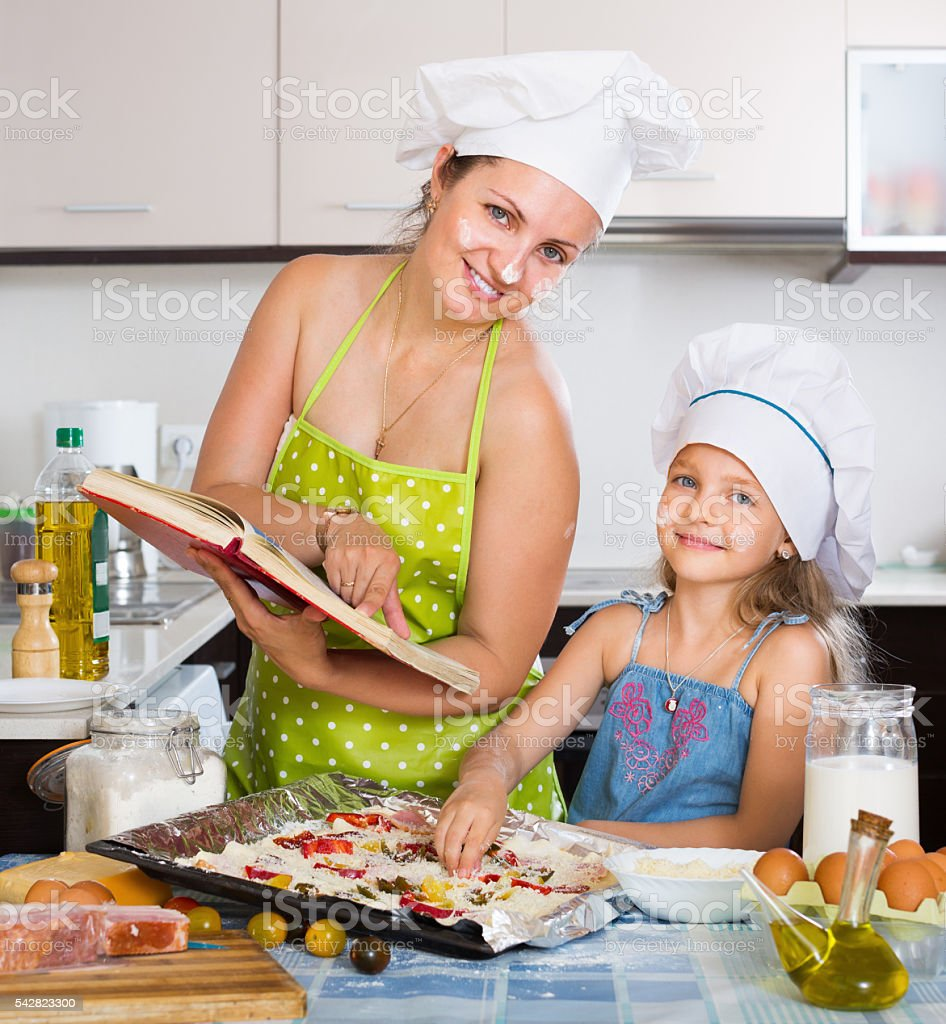 Cute child and mother making a pizza stock photo