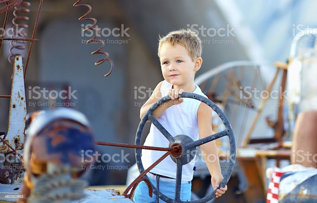 cute child boy pretends driving an imaginary car royalty-free stock photo