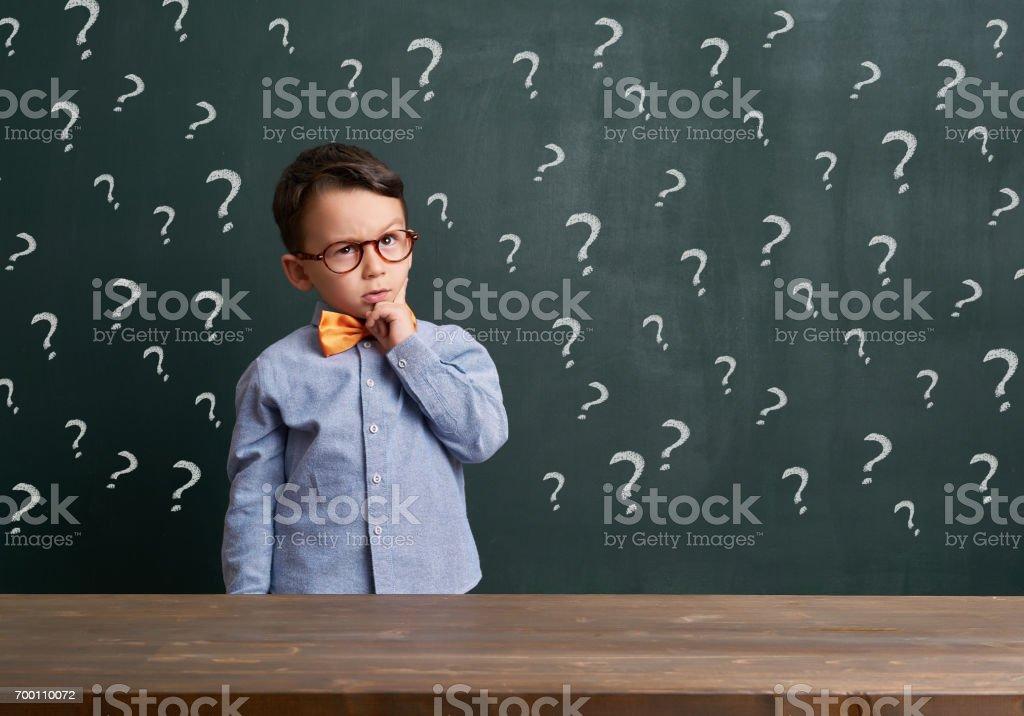 Cute child is in front of chalkboard