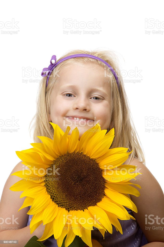 Cute child is smiling and holding a flower (sunflower) stock photo