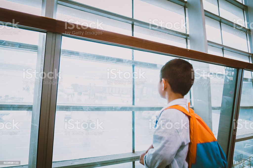 Cute child look outside in airport hall stock photo