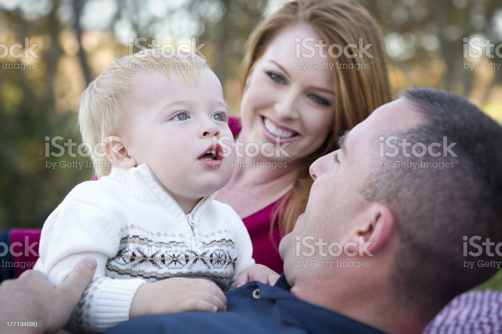 Cute Child Looks Up to Sky as Young Parents Smile royalty-free stock photo