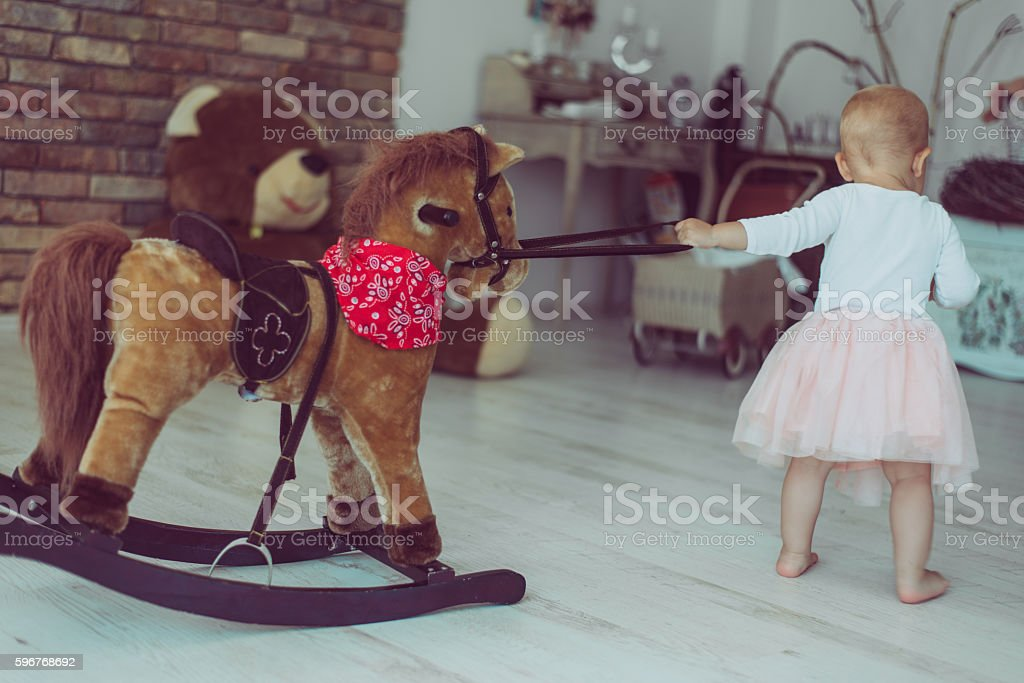 cute child playing with rocking horse stock photo