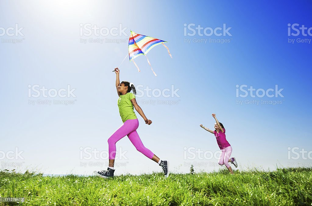 Cute children flying a kite in nature. stock photo