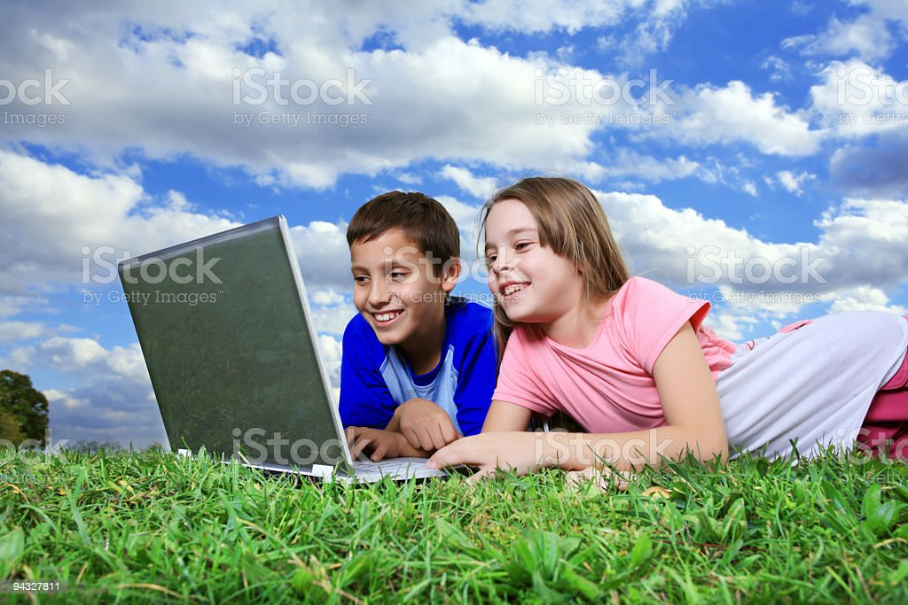 Cute children looking at laptop outdoor. royalty-free stock photo