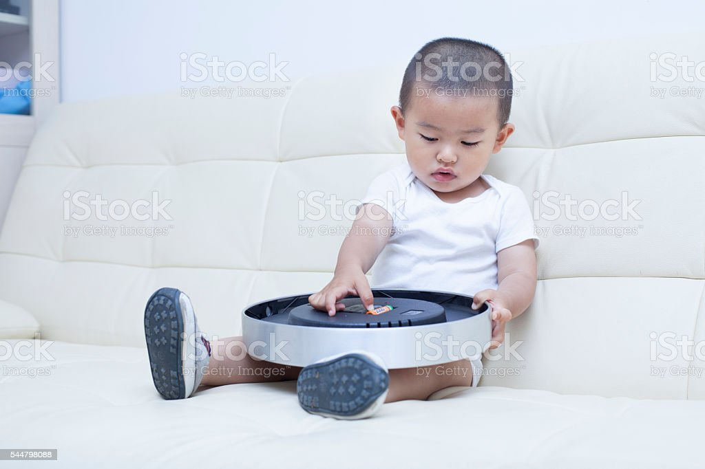 Cute Chinese baby boy playing a clock in sofa stock photo