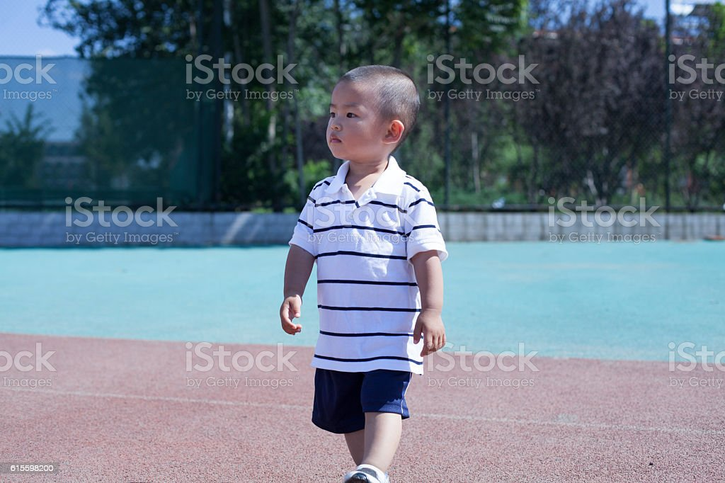 Cute Chinese baby boy playing in a stadium stock photo
