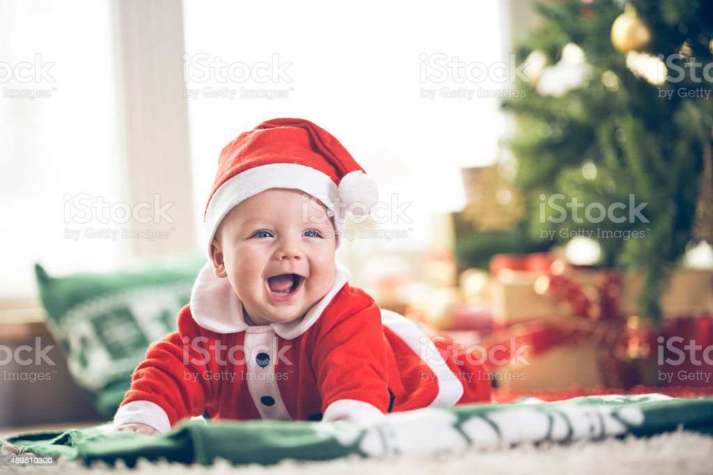 Cute little baby boy in Santa hat and clothes lying down on the green...