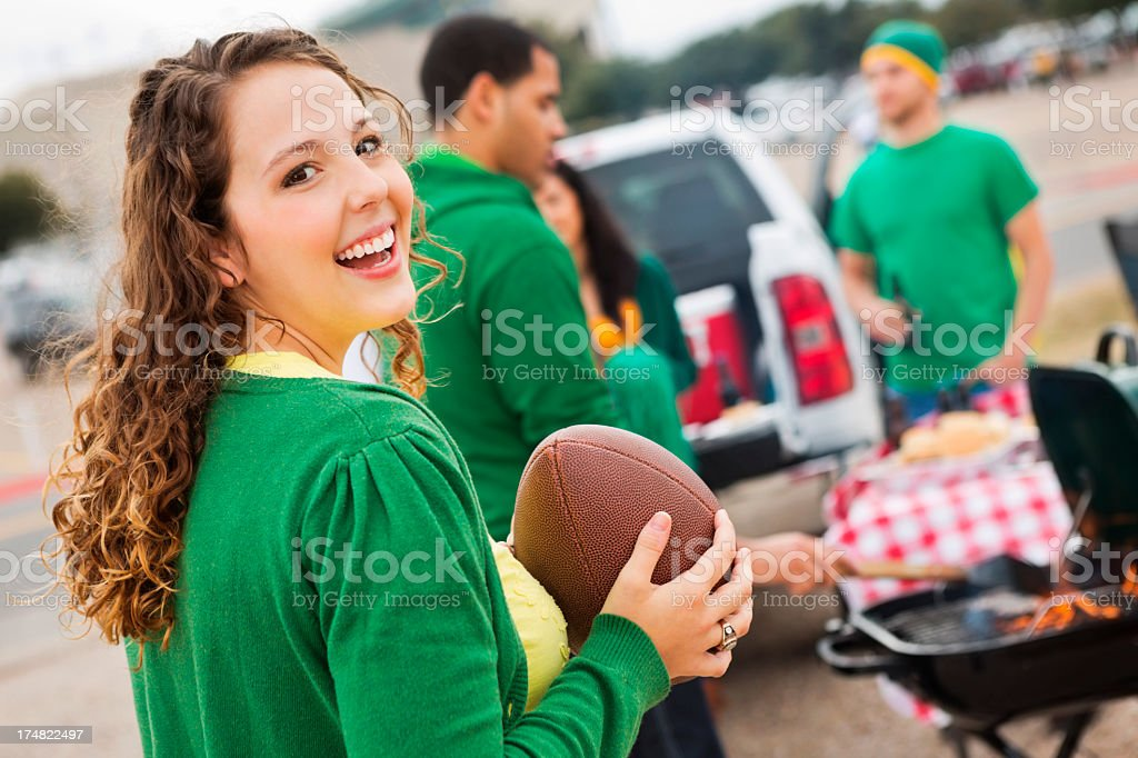 Cute college girl tailgating at stadium with football fans stock photo
