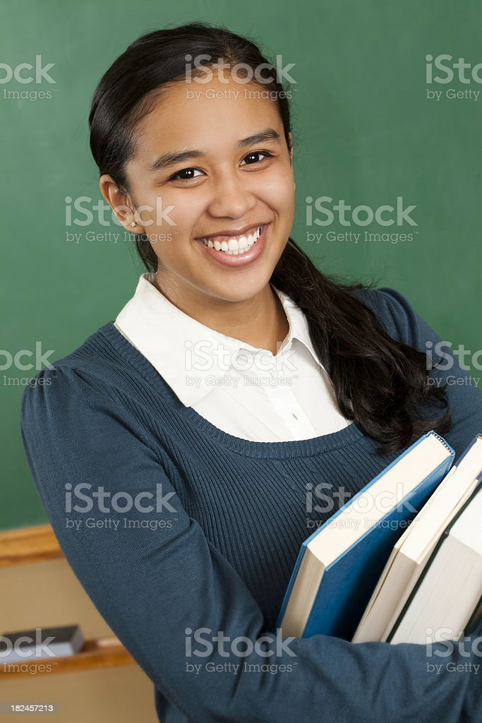 Cute College Student Holding School Books in classroom royalty-free stock photo