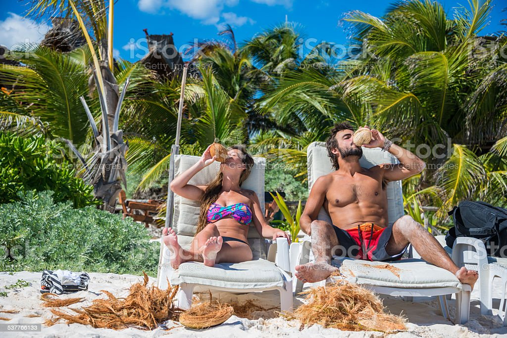 Cute Couple drinking Coconut at Tulum caribbean beach. stock photo