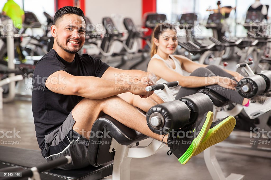 Cute couple exercising together in a gym stock photo
