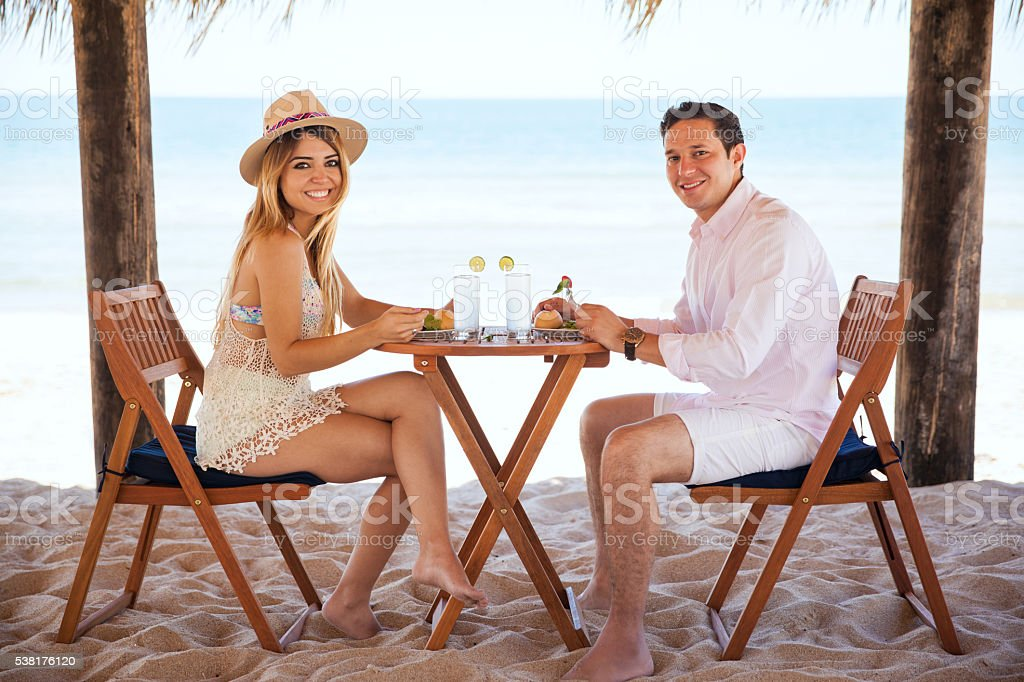 Cute couple in a romantic date at the beach stock photo