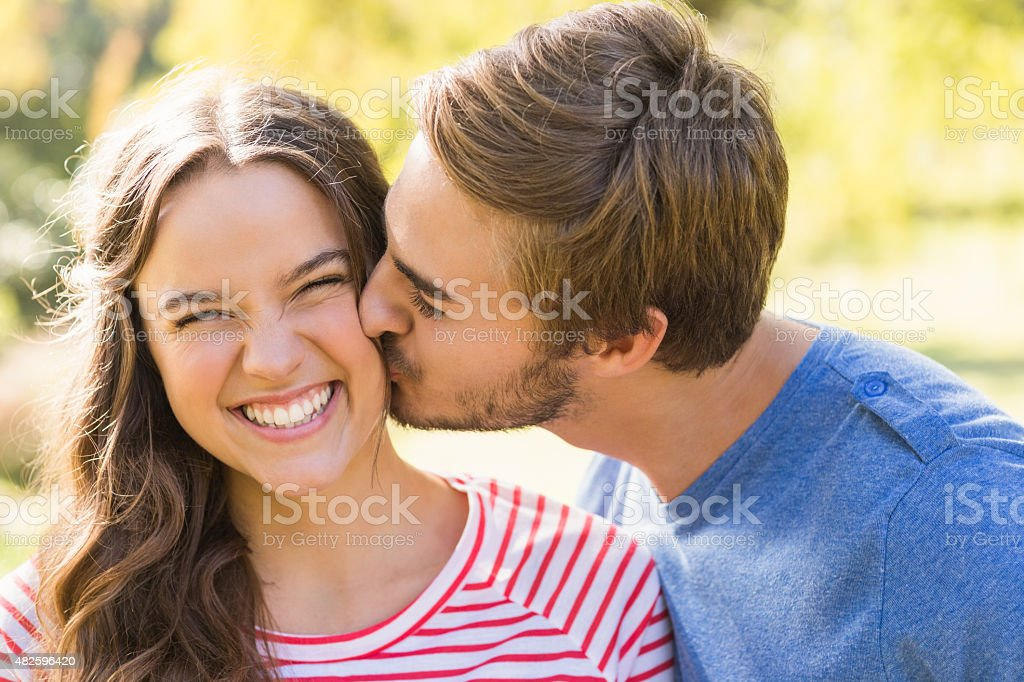 Cute couple kissing in the park stock photo