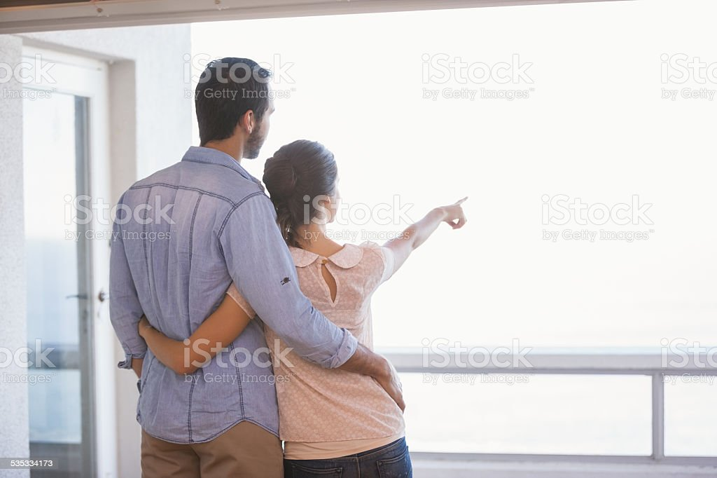 Cute couple looking out the window stock photo
