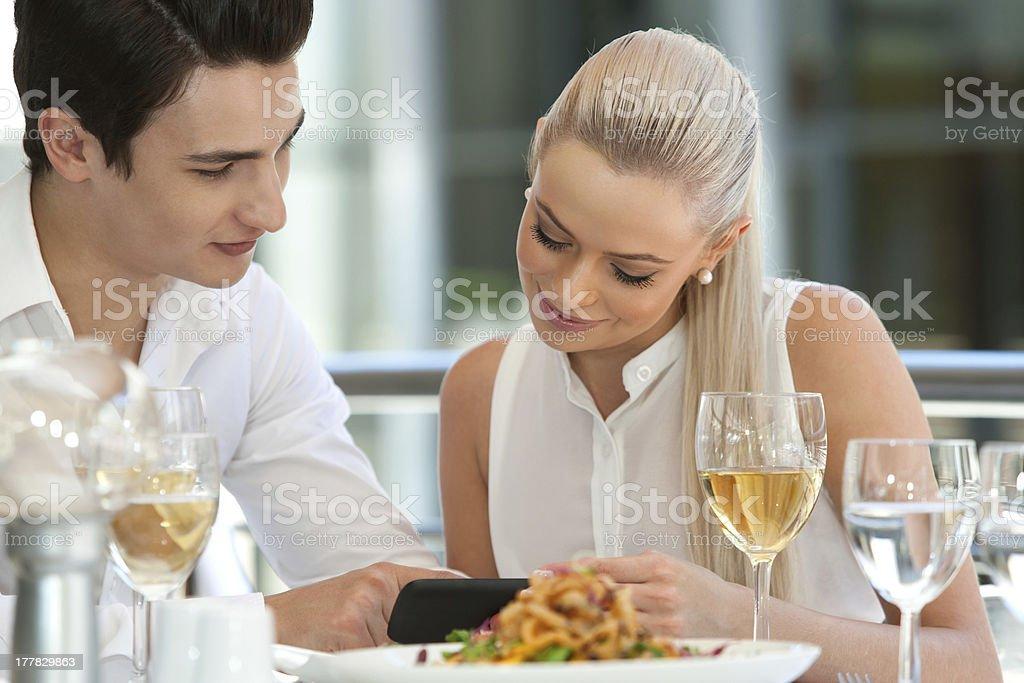 Joli couple jouant avec le téléphone intelligent pour le dîner. photo libre de droits