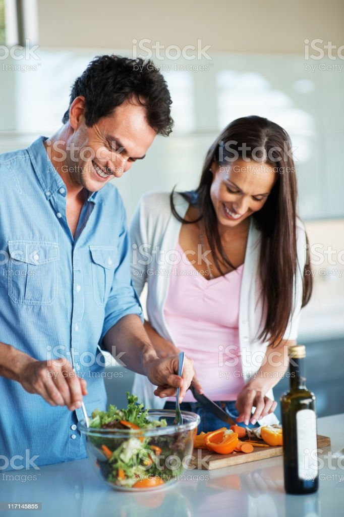 Cute couple preparing salad together royalty-free stock photo
