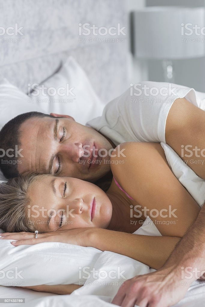 Cute couple sleeping and spooning in bed stock photo