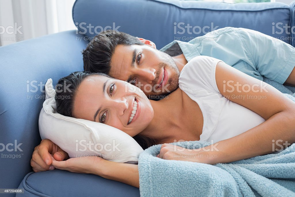 Cute couple spooning on sofa smile to camera stock photo