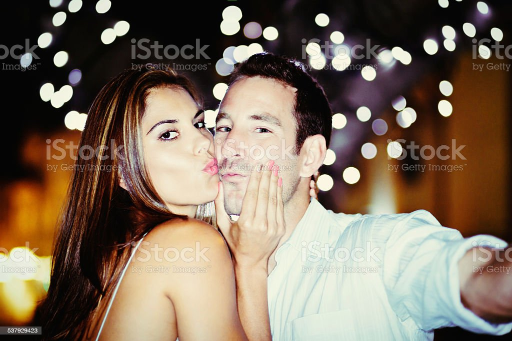 Cute couple take playful trout-pout selfie under twinkling lights stock photo