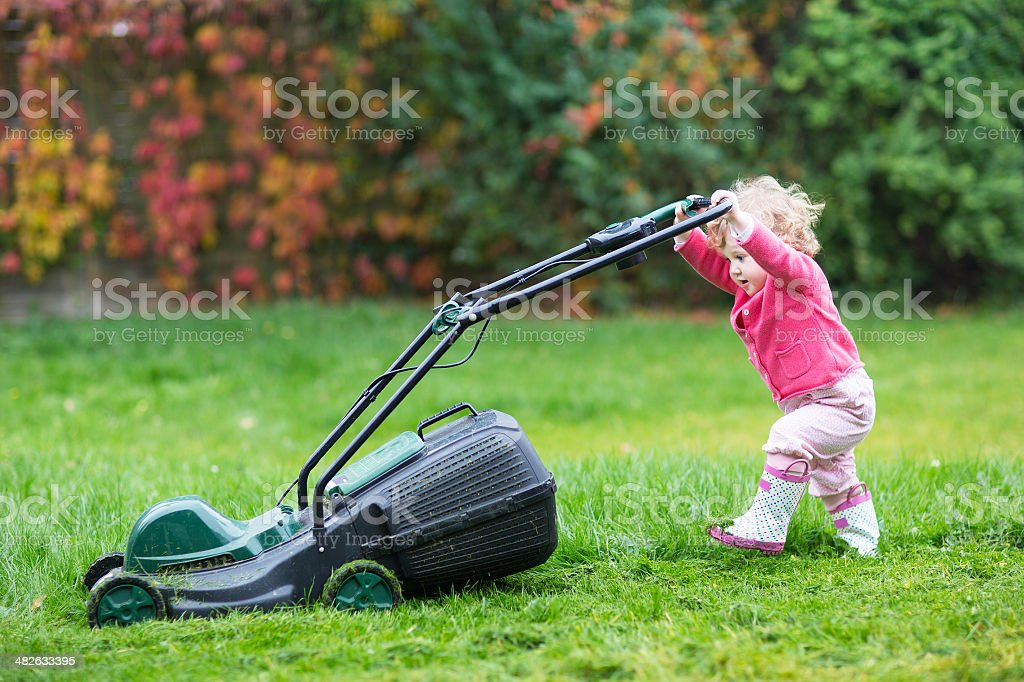 Cute curly baby girl playing with big green lawn mower stock photo