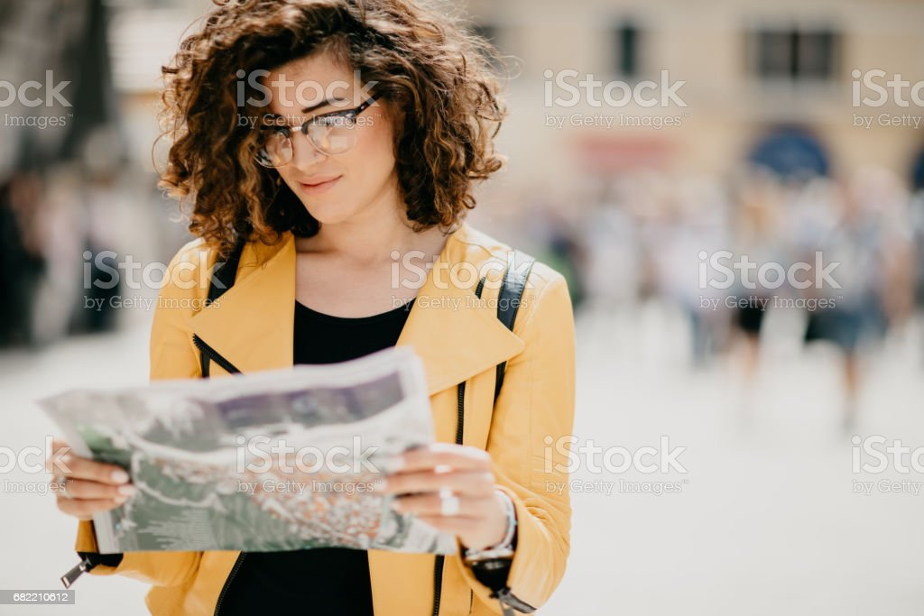Cute curly haired girl with nose piercing looking at the map of the city stock photo