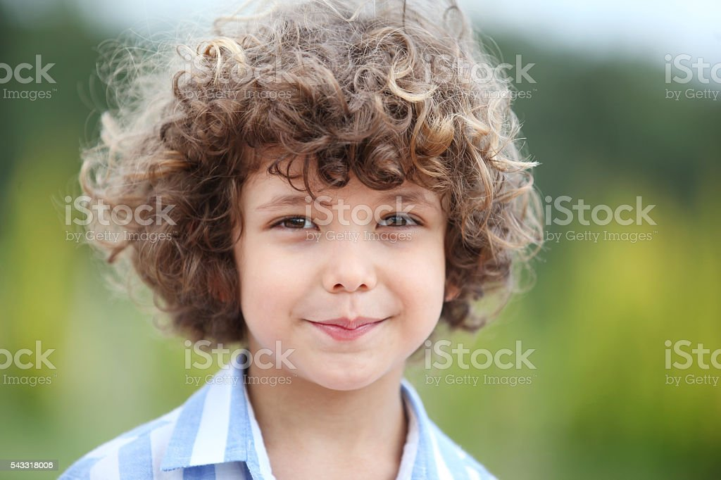Cute curly light brown haired boy stock photo
