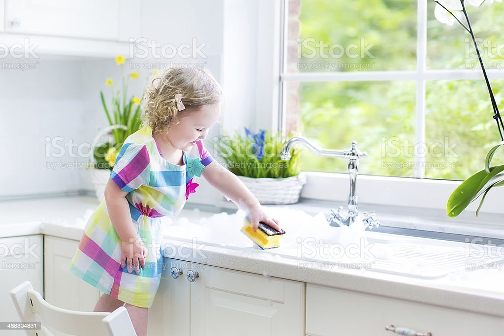 Cute curly toddler girl washing dishes, cleaning with sponge stock photo