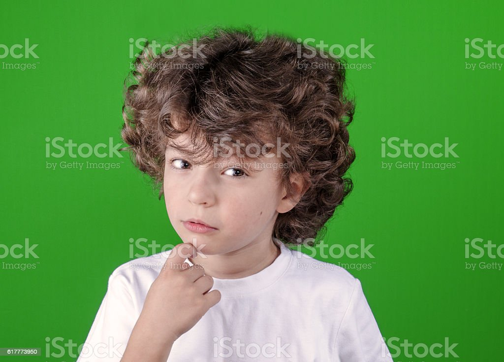 Cute curly-haired boy in a white shirt thoughtfully looking forward. stock photo