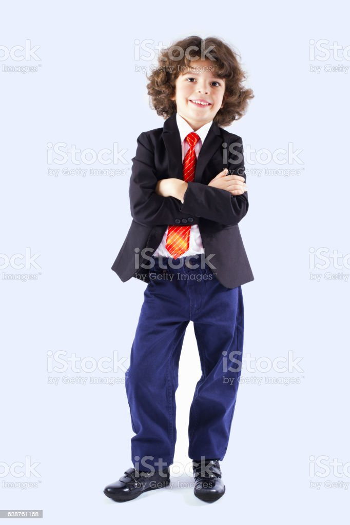 Cute curly-haired boy with his arms folded looking at camera. stock photo