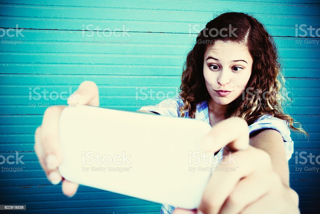 Cute curly-haired girl takes  silly, squinting selfie for fun stock photo