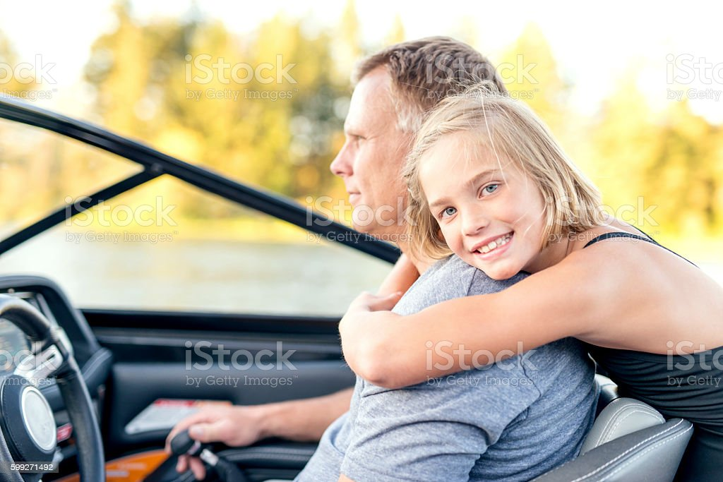 Cute daughter hugging her father stock photo