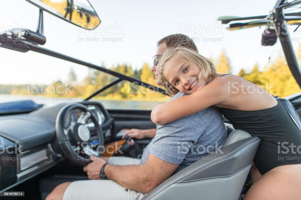 Cute daughter hugs her father on boat stock photo